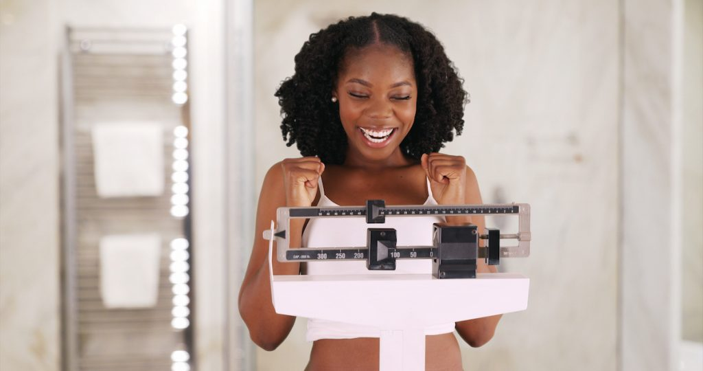 Beautiful black woman happily weighs herself on scale in bathroom; blog: how to set realistic weight loss goals