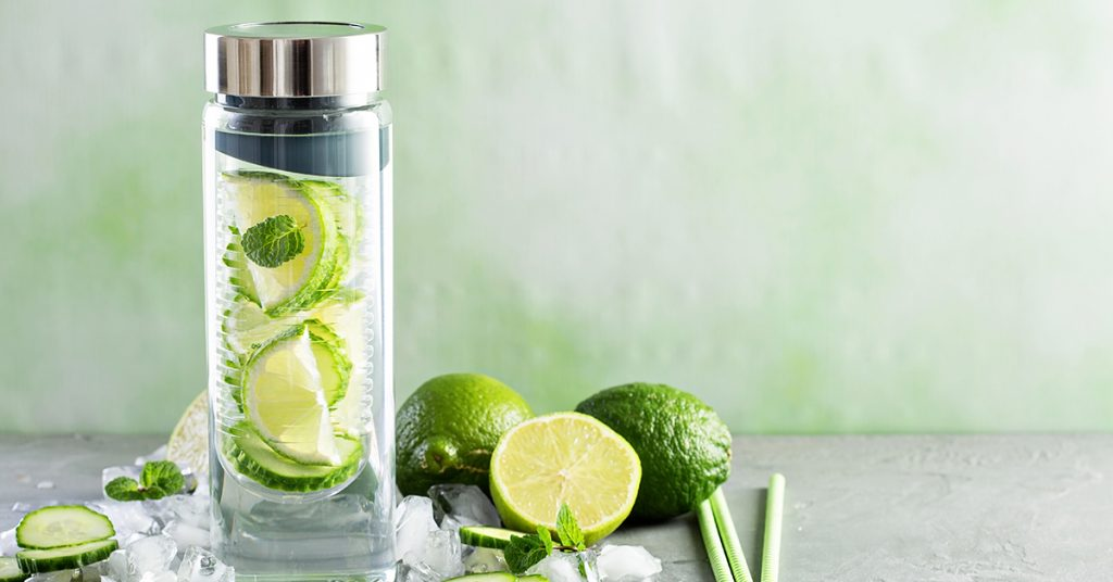Infused water with lime and cucumber in a glass bottle; blog: 10 Fruit-Infused Water Recipes to Help You Stay Hydrated