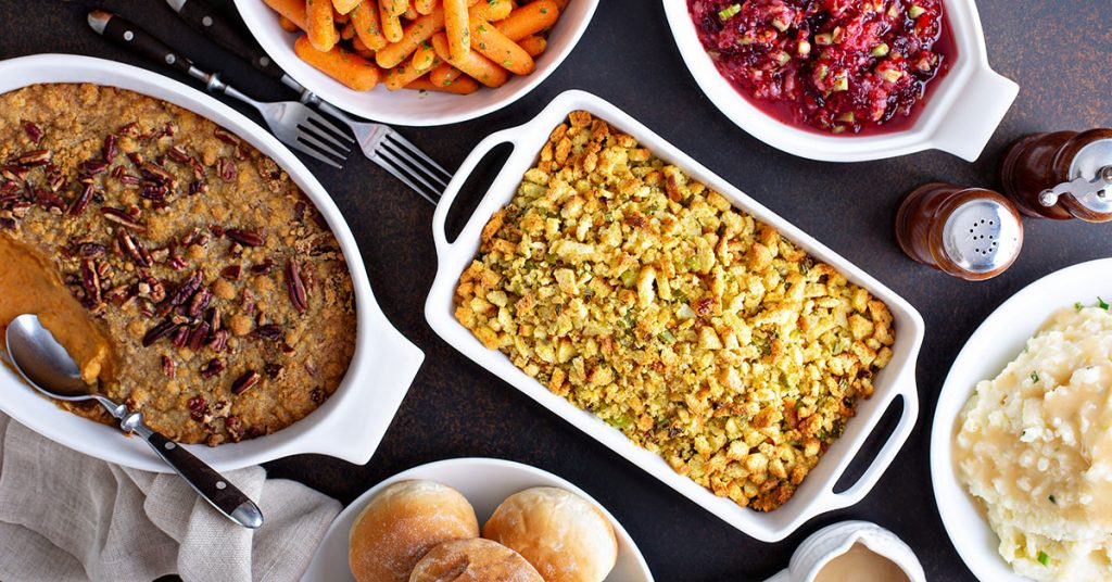 Variety of Thanksgiving sides on the dinner table, carrots, mashed potatoes, sweet potato casserole and stuffing; blog: healthy side dishes for the holidays
