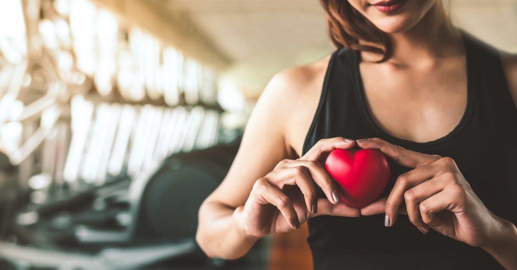 Happy sport woman holding red heart in fitness gym club. Medical cadio heart strength training lifestyle. Pretty female sport girl workout exercise. Cardiac healthy and wellbeing. Massage ball in hand; blog: Weight Loss and Heart Health