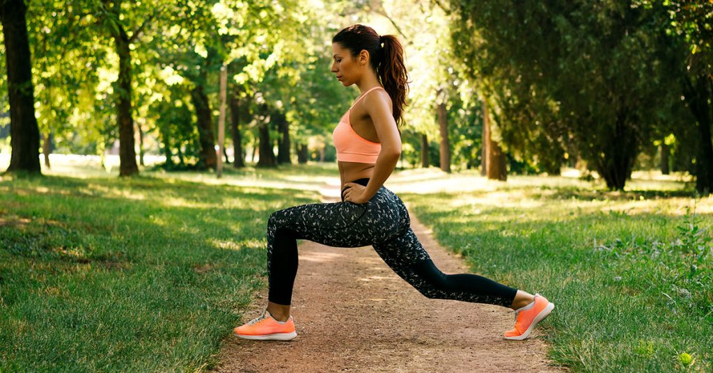 Pretty woman doing exercises in the park; blog: Outdoor Exercise Ideas for Spring